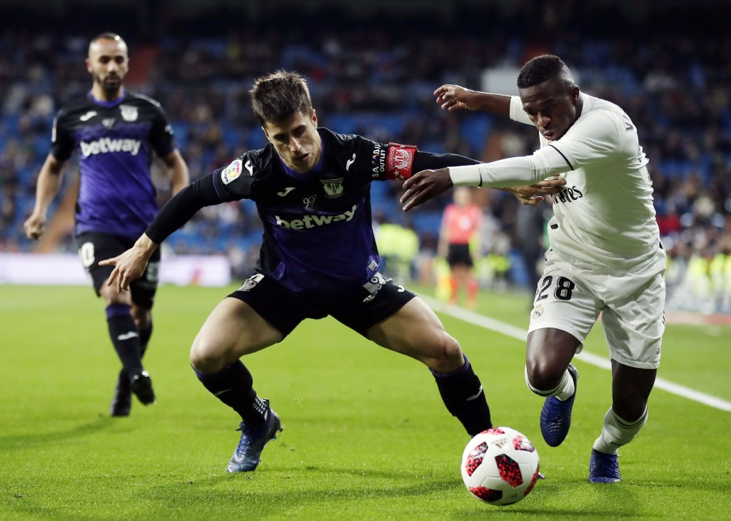 Real Madrid's Vinicius Jr, right, duels for the ball with Leganes' Unai Bustinza during a Spanish Copa del Rey soccer match between Real Madrid and Le