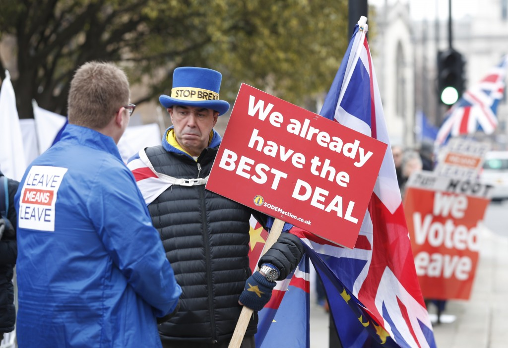 Pro-Brexit, left, and anti-Brexit, right, protesters debate their views outside parliament in London, Thursday Jan. 10, 2019. Prime Minister Theresa M