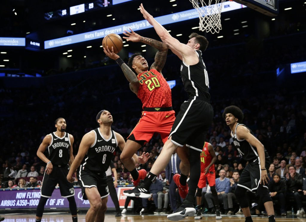 Atlanta Hawks' John Collins (20) shoots as Brooklyn Nets' Rodions Kurucs (00) defends, while Jared Dudley (6) and Spencer Dinwiddie (8) watch during t...