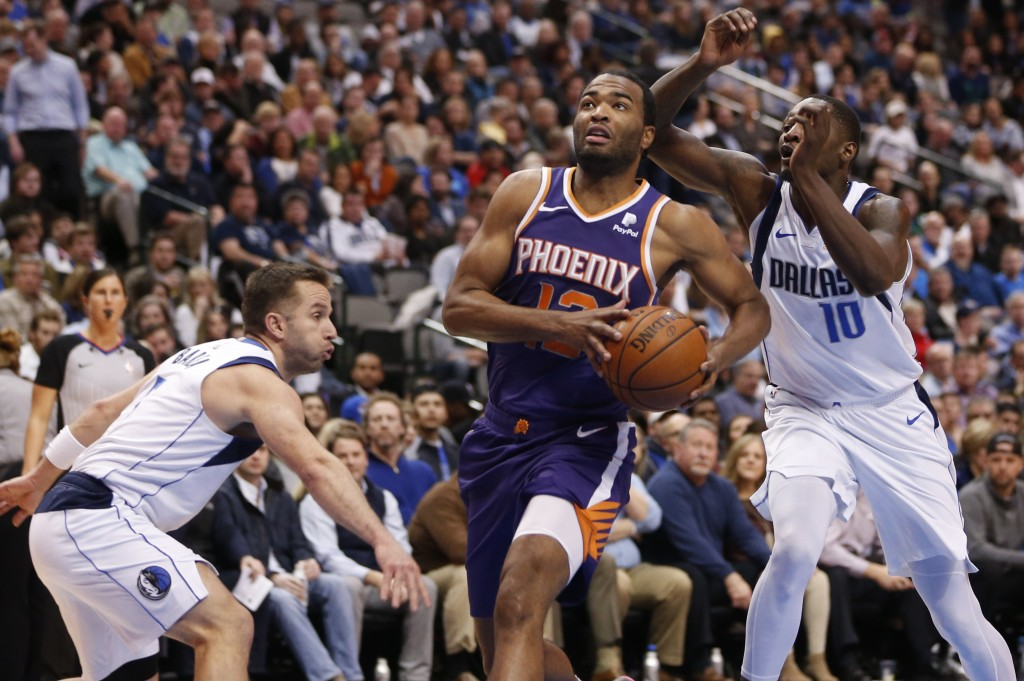 Phoenix Suns forward T.J. Warren (12) drives the ball past Dallas Mavericks forward Dorian Finney-Smith (10) and guard J.J. Barea, left, during the fi...