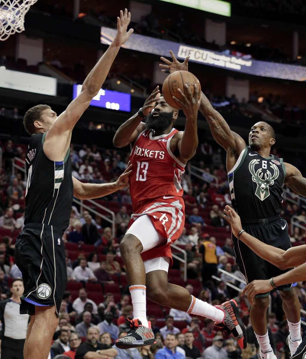 Houston Rockets guard James Harden (13) puts up a shot between Milwaukee Bucks center Brook Lopez (11) and guard Eric Bledsoe (6) during the first hal...