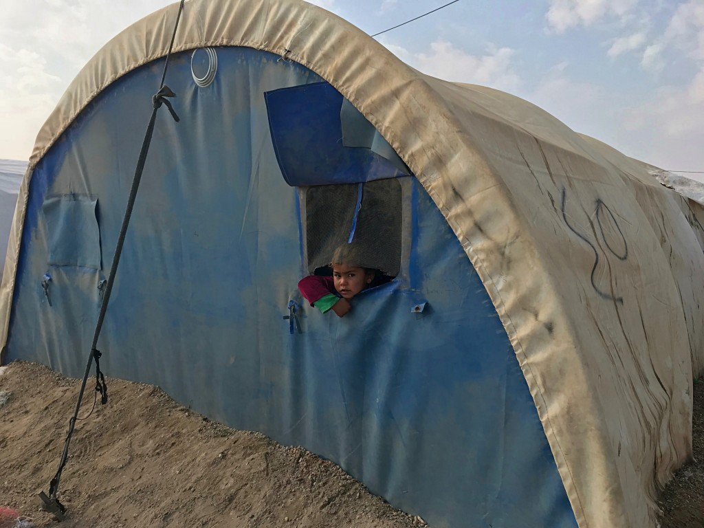 In this Dec. 26, 2018 photo, a girl peers out from her family's tent at the Amariyat al-Fallujah camp, in Anbar province, Iraq. A little over a year s...