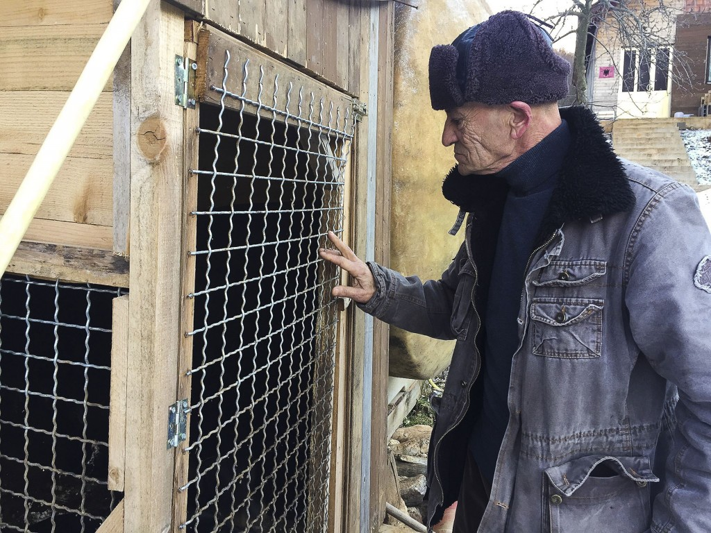 In this Monday, Jan. 7, 2019 photo, former Kosovo Liberation Army fighter Sabahajdin Cena looks at his dog's kennel, in the town of Rahovec. Two decad