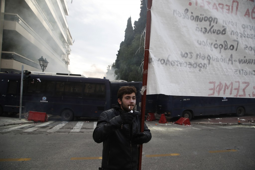 A protester smokes a cigarette after clashes near the Prime Minister's office in Athens, Friday, Jan. 11, 2019. About 1,500 people took part in the pr
