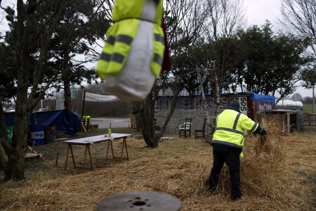 A protestor wearing yellow vests scatters straw in a makeshift camp on a roundabout near Senlis, north of Paris, Thursday, Jan. 10, 2019. With its mak