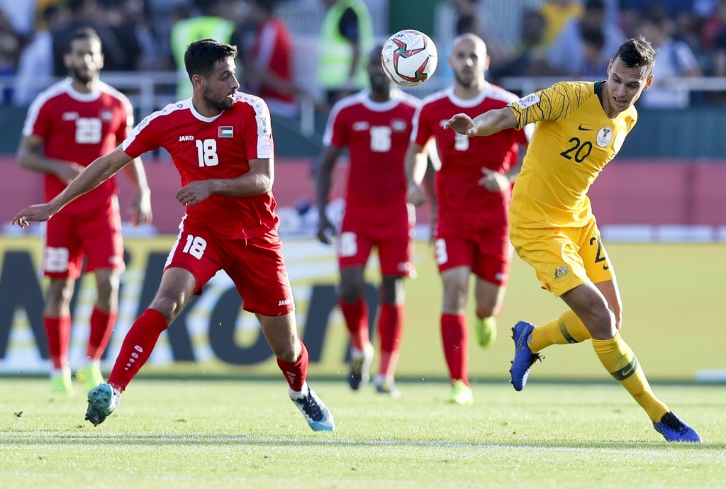 Australia's defender Trent Sainsbury , right, and Palestine's defender Day Dabbagh go for the balld uring the AFC Asian Cup group B soccer match betwe