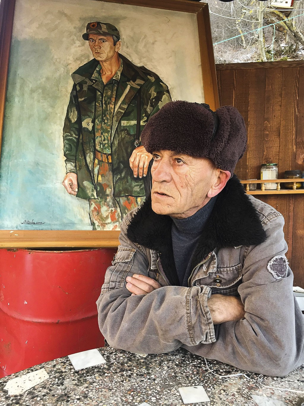 In this Monday, Jan. 7, 2019 photo, former Kosovo Liberation Army fighter Sabahajdin Cena poses for a photo in front of a painted portrait of himself,