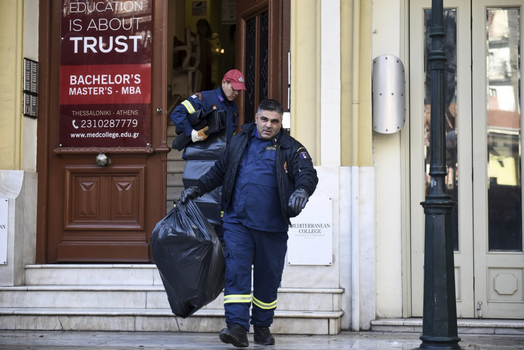A firefighter leaves a college, holding a plastic bag after employees received suspicious envelopes in the northern port city of Thessaloniki, Greece,