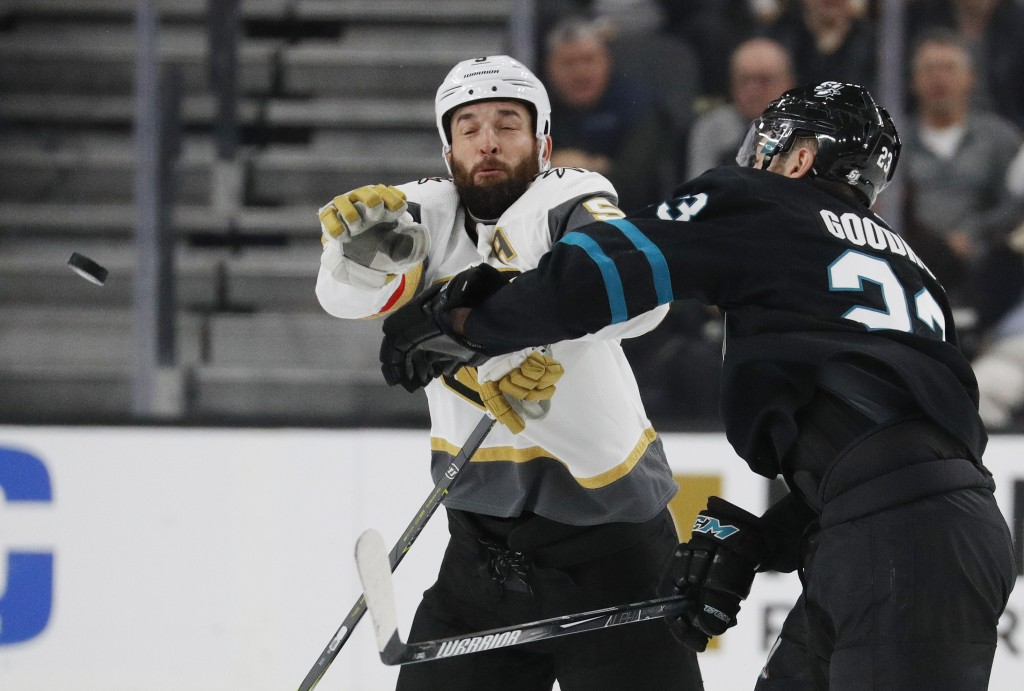 San Jose Sharks right wing Barclay Goodrow, right, and Vegas Golden Knights defenseman Deryk Engelland try to knock the puck out of the air during the