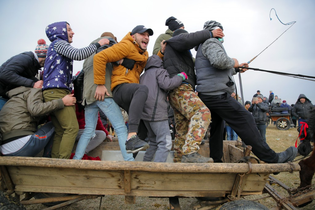 In this Sunday, Jan. 6, 2019, photograph people cheer while riding in a horse down cart past an Orthodox priest sprinkling holy water on horses and pe