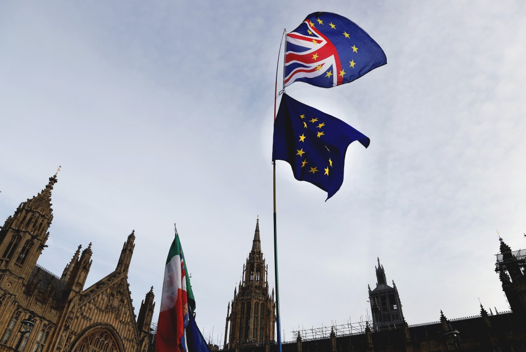 A Pro-European demonstrator raises flags to protest outside parliament in London, Friday, Jan. 11, 2019. Britain's Prime Minister Theresa May is strug