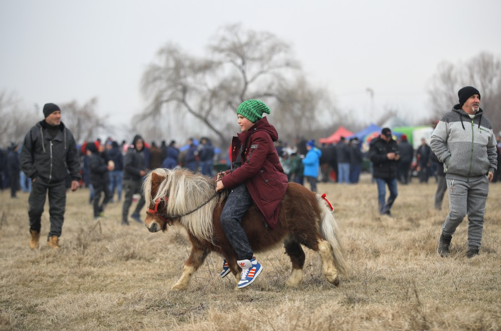 In this Sunday, Jan. 6, 2019, photograph a child rides a pony during Epiphany celebrations in Pietrosani, Romania. Epiphany celebrations bring togethe
