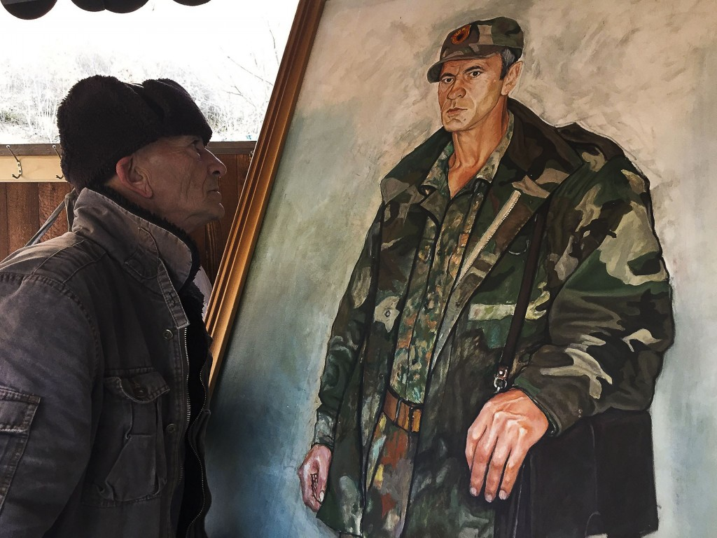 In this Monday, Jan. 7, 2019 photo, former Kosovo Liberation Army fighter Sabahajdin Cena looks a painted portrait of himself, in the town of Rahovec.