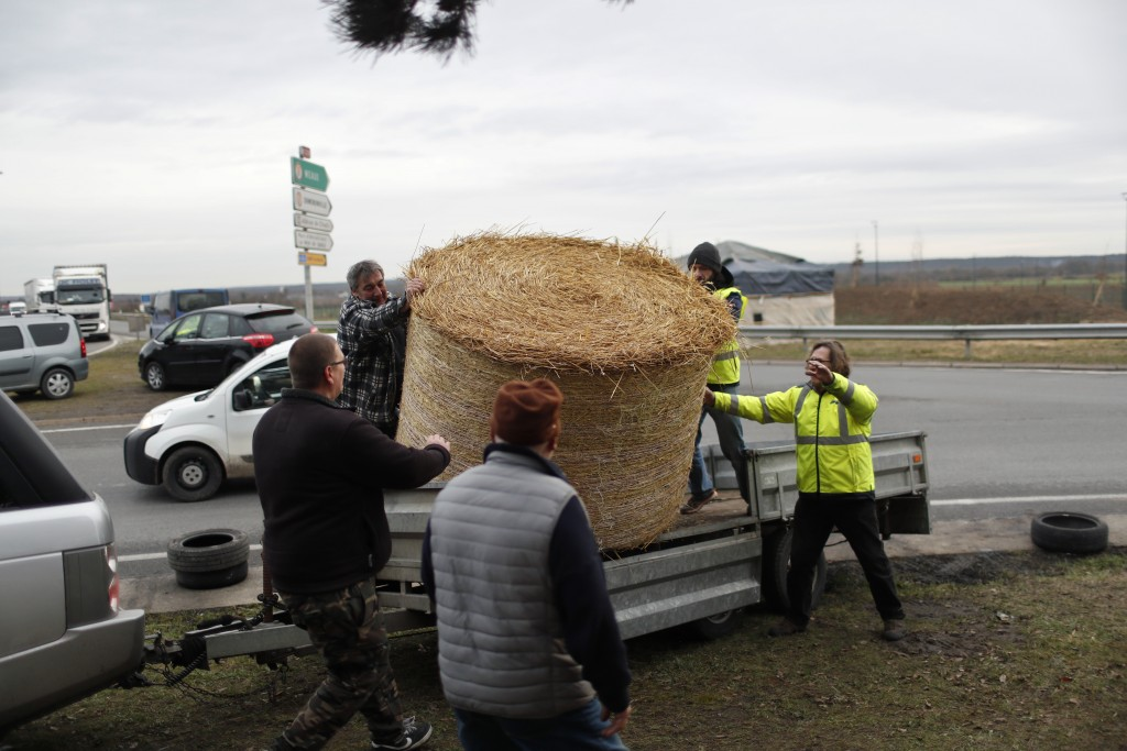 Protestors wearing yellow vests unload a bale of straw from a trailer on a roundabout near Senlis, north of Paris, Thursday, Jan. 10, 2019. With its m