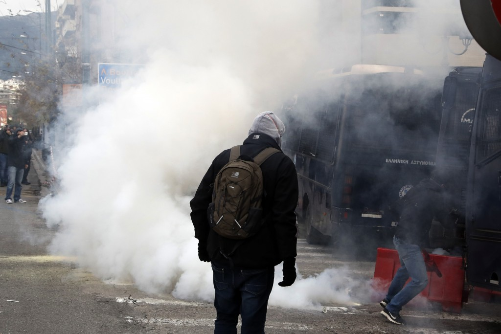 Riot police throw a tear gas canister at teachers and other protesters, during clashes near the Prime Minister's office in Athens, Friday, Jan. 11, 20