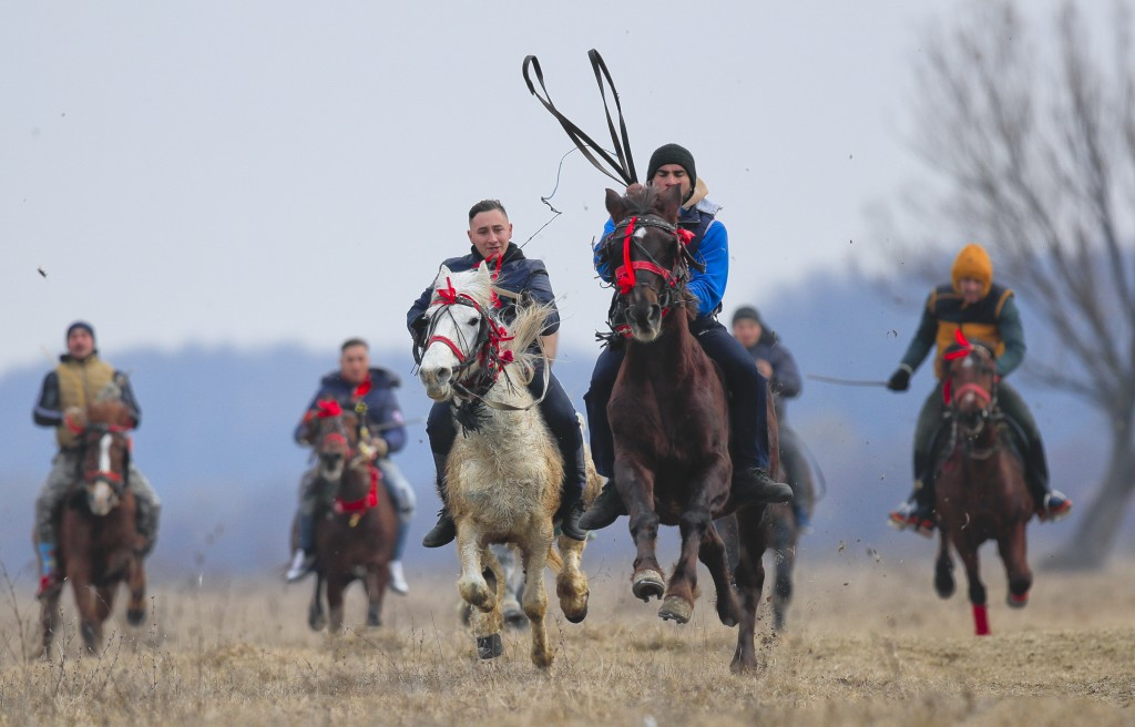 In this Sunday, Jan. 6, 2019, villagers compete in an Epiphany celebration horse race in Pietrosani, Romania. The horse race tradition started in the