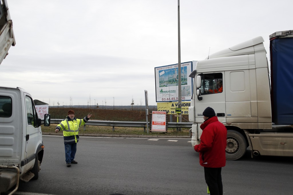 Yellow vest protestor Michel, no family name available, directs the traffic on a roundabout near Senlis, north of Paris, Thursday, Jan. 10, 2019. With