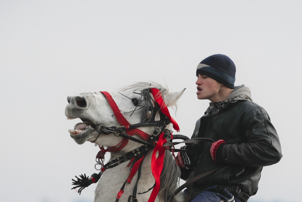 In this Sunday, Jan. 6, 2019, a man struggles to control his horse before an Epiphany celebration horse race in Pietrosani, Romania. (AP Photo/Vadim G