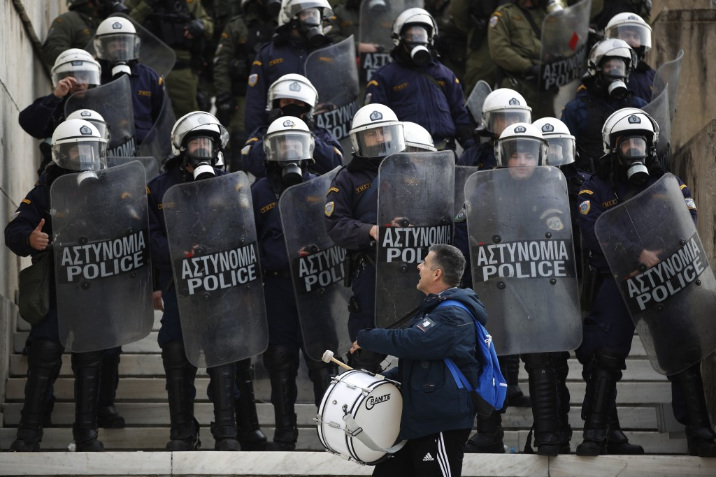 A protester shouts at riot police during a rally outside the Greek Parliament in Athens, Friday, Jan. 11, 2019. About 1,500 people took part in the pr