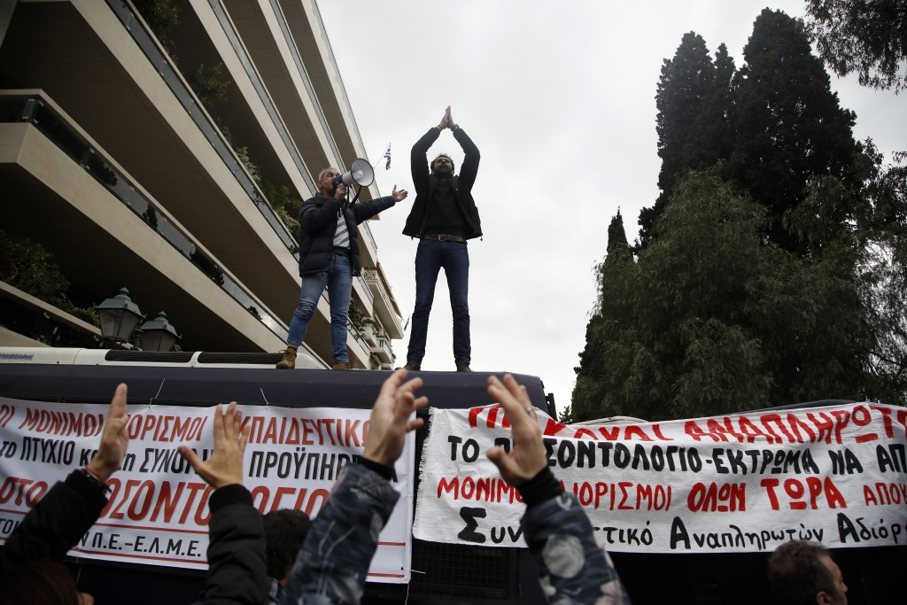 Protesters shout slogans on top of police buses during a protest near the Prime Minister's office in Athens, Friday, Jan. 11, 2019. About 1,500 people