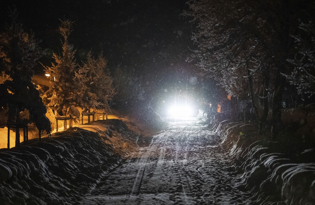 A car drives on a snow covered street at the Bavarian city Berchtesgaden, Germany, Friday, Jan 11, 2018, after Austria and southern Germany were hit b