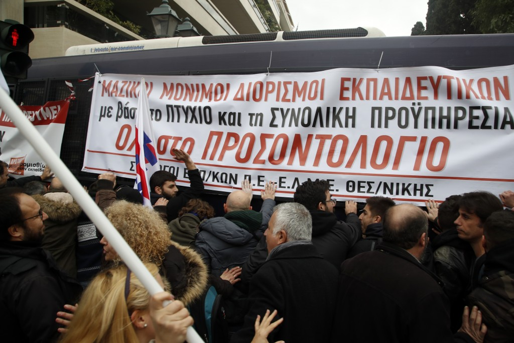 Teachers and other protesters push police buses during clashes near the Prime Minister's office in Athens, Friday, Jan. 11, 2019. About 1,500 people t