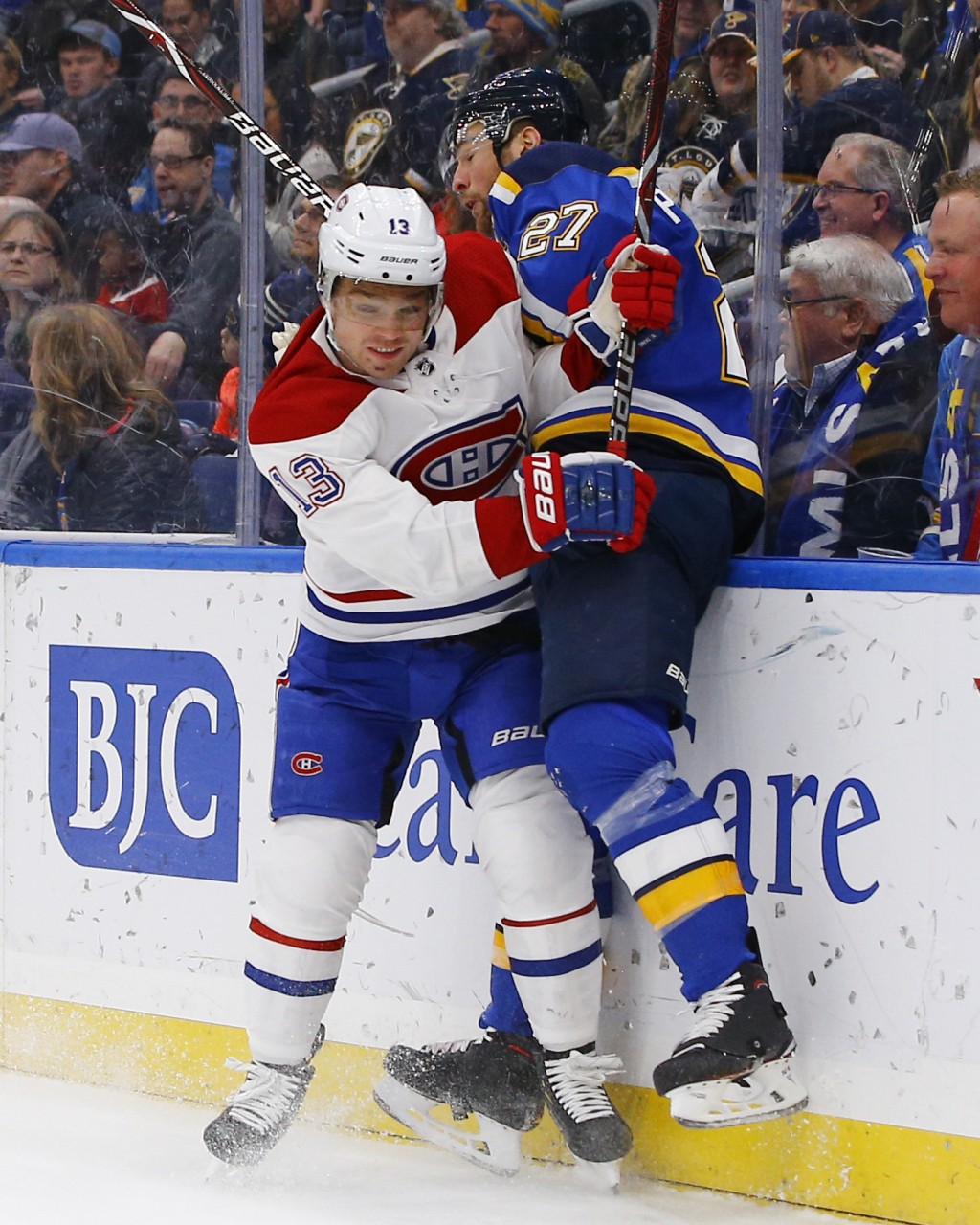 Montreal Canadiens' Max Domi, left, checks St. Louis Blues' Alex Pietrangelo into the boards during the first period of an NHL hockey game Thursday, J