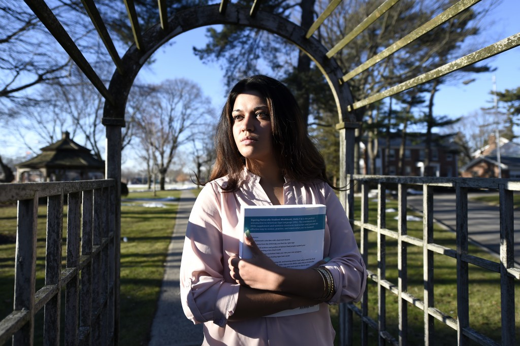 FILE - In this Feb. 2, 2016, file photo, Naila Amin, 26, holds a book from one of the classes she was taking at Nassau Community College in Garden Cit...