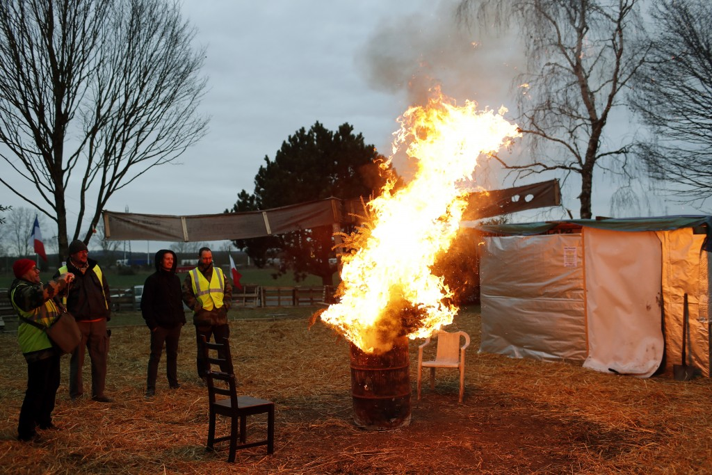 Protestors wearing yellow vests stand next to a fire in a makeshift camp on a roundabout near Senlis, north of Paris, Thursday, Jan. 10, 2019. With it