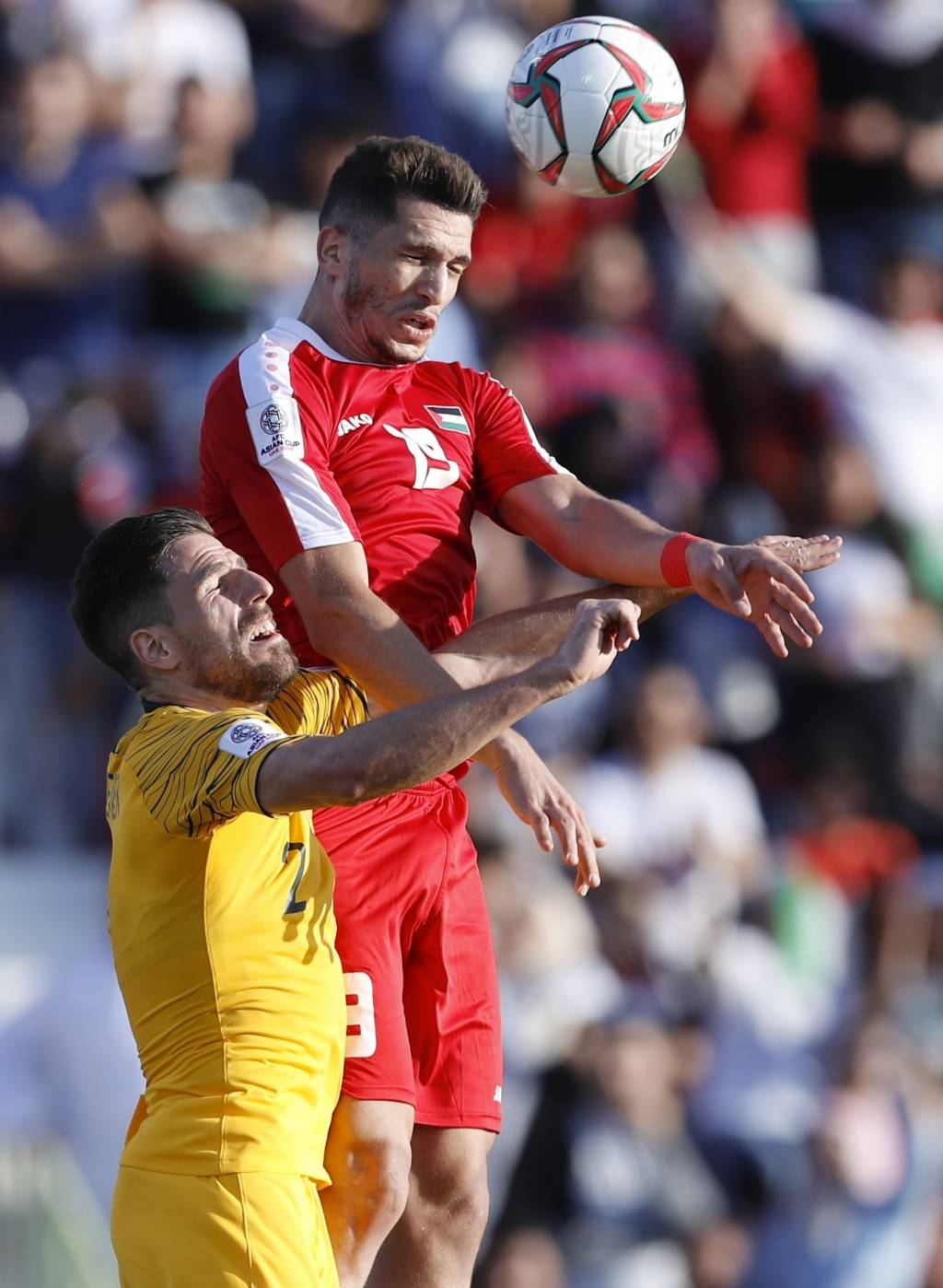 Palestine forward Mahmoud Wadi, top, and Australia defender Milos Degenek vie for the ball during the AFC Asian Cup group B soccer match between Austr