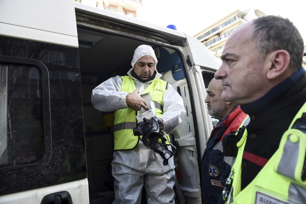 Paramedics prepare to enter a college after employees received a suspicious envelope,  in the northern port city of Thessaloniki, Greece, Friday, Jan.