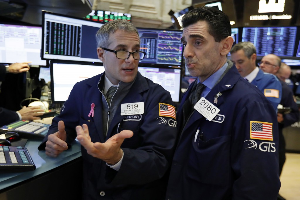 FILE- In this Jan. 4, 2019, file photo specialists Anthony Rinaldi, left, and Peter Mazza confer as they work on the floor of the New York Stock Excha