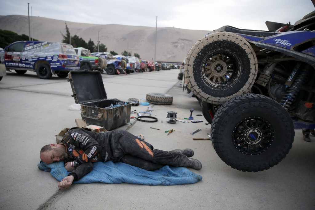 Co-driver Bill Conger, of United States, rests next to his Tetron prior to the stage five of the Dakar Rally between Tacna and Arequipa, Peru, Friday,