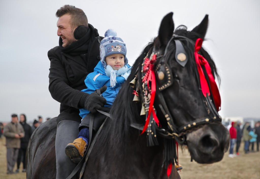 In this Sunday, Jan. 6, 2019, photograph a man rides a horse along with a baby during Epiphany celebrations in Pietrosani, Romania. (AP Photo/Vadim Gh