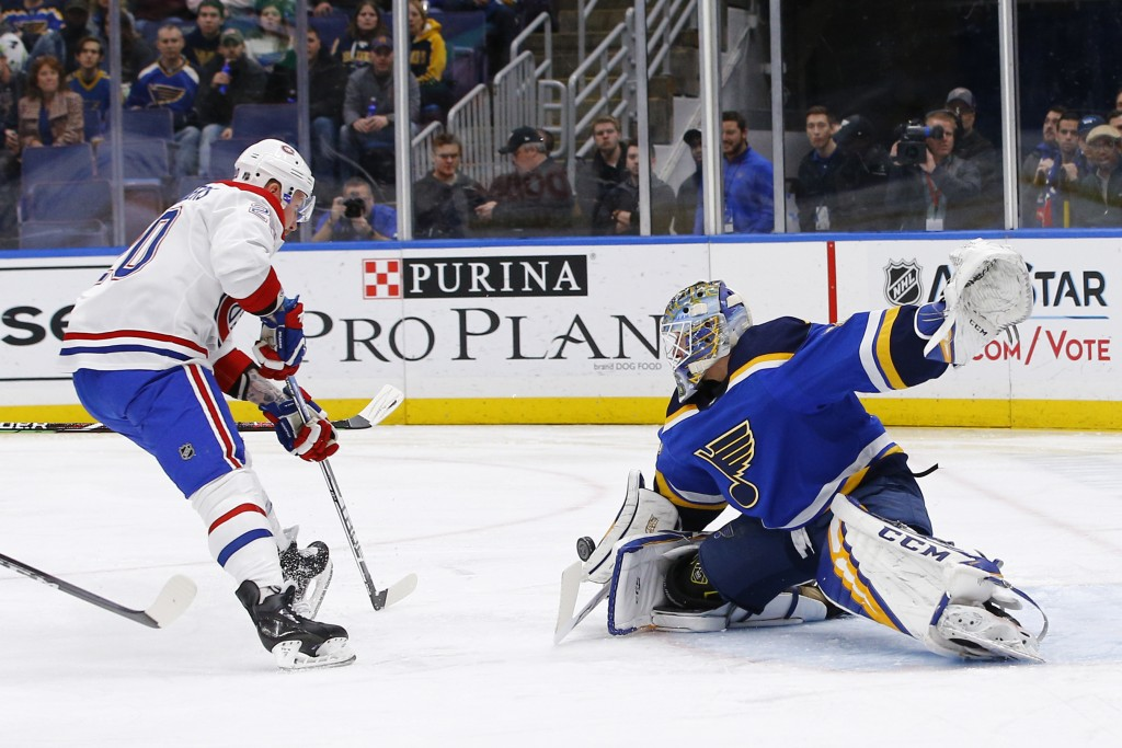 St. Louis Blues goaltender Jordan Binnington stops a shot by Montreal Canadiens' Nicolas Deslauriers, left, during the first period of an NHL hockey g