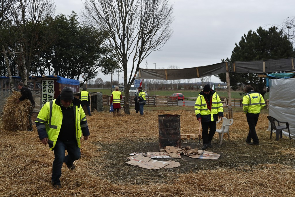 Protestors wearing yellow vests stand in a makeshift camp on a roundabout near Senlis, north of Paris, Thursday, Jan. 10, 2019. With its makeshift gro