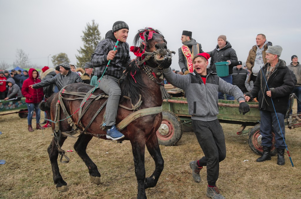 In this Sunday, Jan. 6, 2019, photograph a man rides his horse by an Orthodox priest sprinkling holy water on animals and people before an Epiphany ce