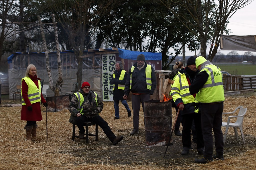 Martine, left, Claude, second left, and other protestors wearing yellow vests gather in a makeshift camp on a roundabout near Senlis, north of Paris,