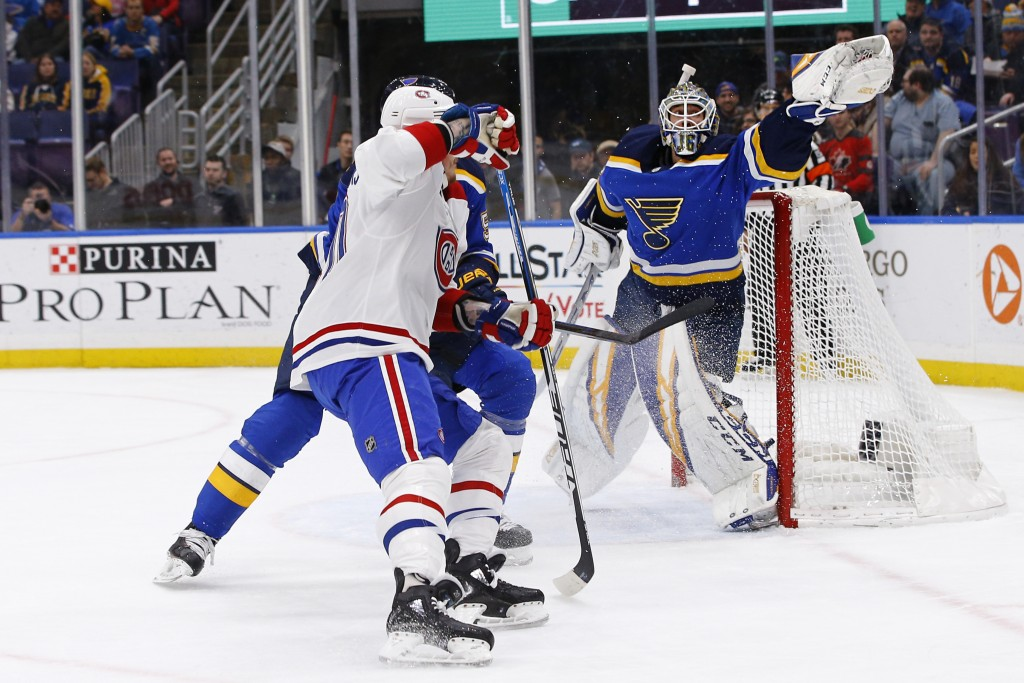 St. Louis Blues goaltender Jordan Binnington reaches for the puck after it was deflected by Montreal Canadiens' Nicolas Deslauriers, front, and Blues