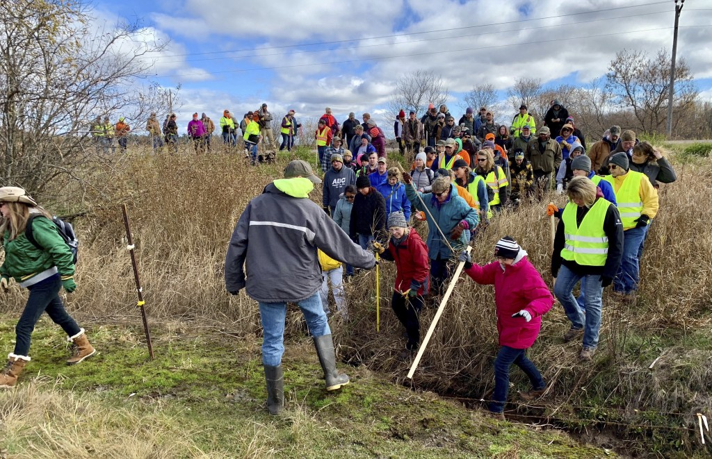 FILE - In this Oct. 23, 2018, file photo, volunteers cross a creek and barbed wire near Barron, Wis., on their way to a ground search for 13-year-old