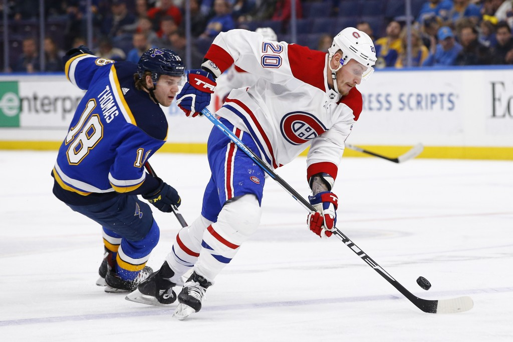 Montreal Canadiens' Nicolas Deslauriers, right, handles the puck as he is pressured by St. Louis Blues' Robert Thomas during the first period of an NH