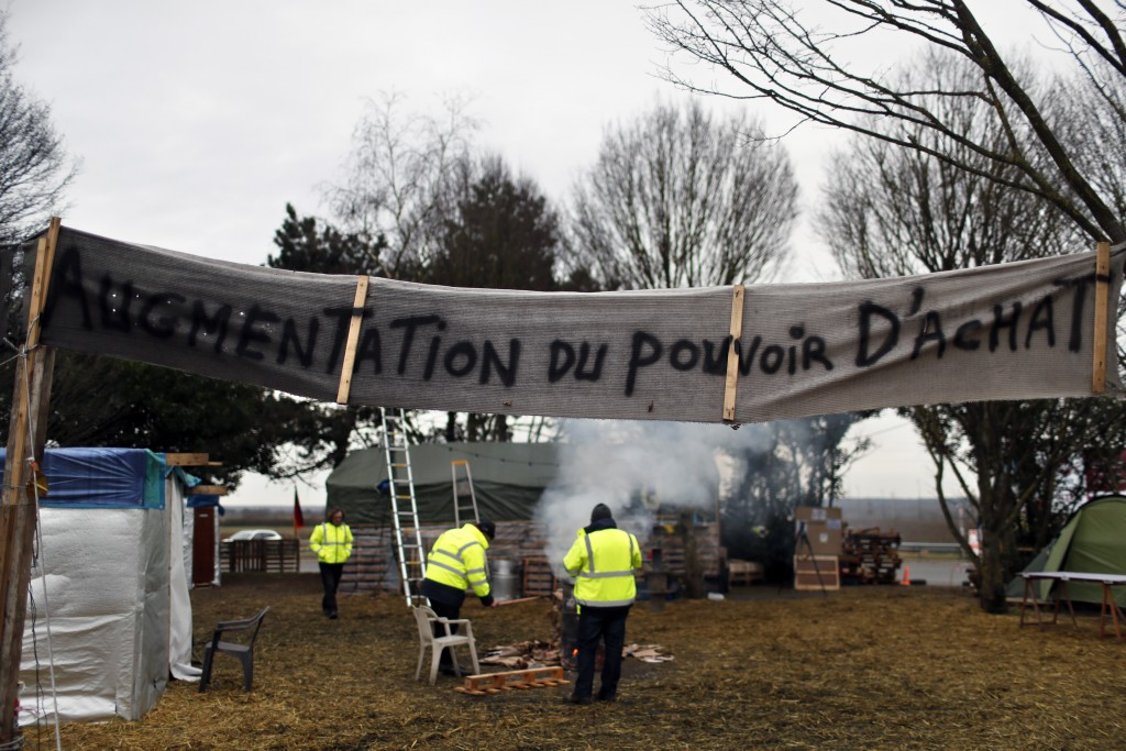 "A banner reads ""increase in purchasing power"" in a makeshift camp on a roundabout occupied by yellow vests protestors near Senlis, north of Paris, Thu"