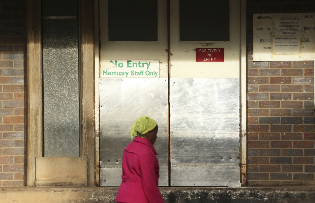 In this Jan. 9, 2019, photo, a woman walks past the mortuary entrance where a family collected the body of their son who died at Parirenyatwa Hospital