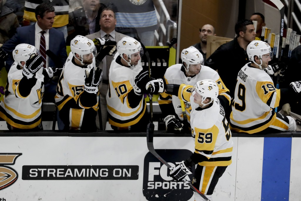 Pittsburgh Penguins left wing Jake Guentzel is congratulated after scoring against the Anaheim Ducks during the second period of an NHL hockey game in