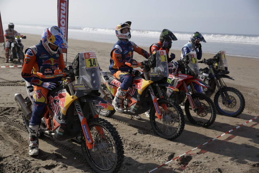 Toby Price of Australia, second from right, sits on his KTM motorbike next to teammate Sam Sunderland of Great Britain, left, at the start of stage fi