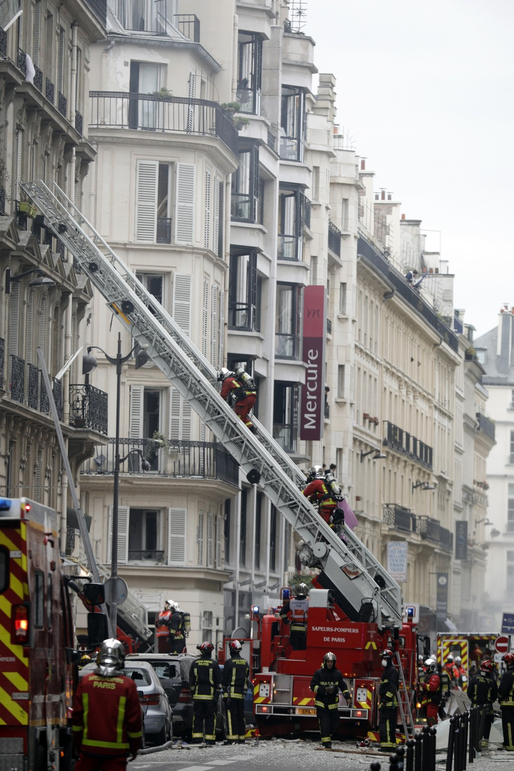 Firefighters work at the scene of a gas leak explosion in Paris, France, Saturday, Jan. 12, 2019. Paris police say several people have been injured in