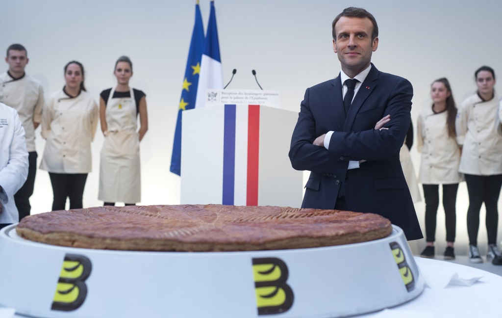 French President Emmanuel Macron poses next to a traditional epiphany cake at the Elysee Palace in Paris, France, Friday, Jan. 11, 2019. (Ian Langsdon