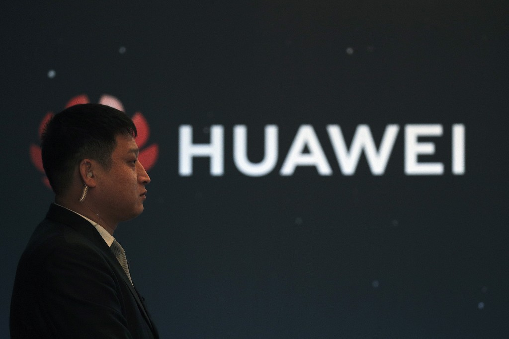 In this Jan. 9, 2019, photo, a security guard stands near the Huawei company logo during a new product launching event in Beijing. The Chinese Foreign