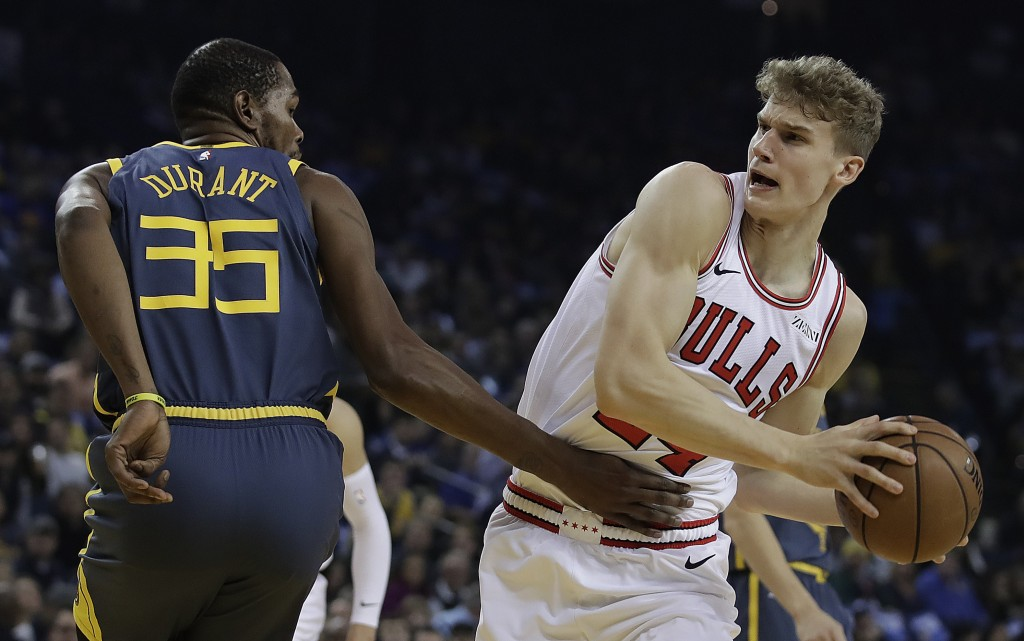 Chicago Bulls' Lauri Markkanen, right, keeps the ball from Golden State Warriors' Kevin Durant (35) during the first half of an NBA basketball game Fr