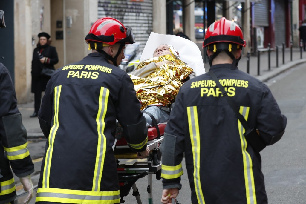 Firefighters evacuate a wounded man on a stretcher from the scene of a gas leak explosion in Paris, France, Saturday, Jan. 12, 2019. A powerful explos